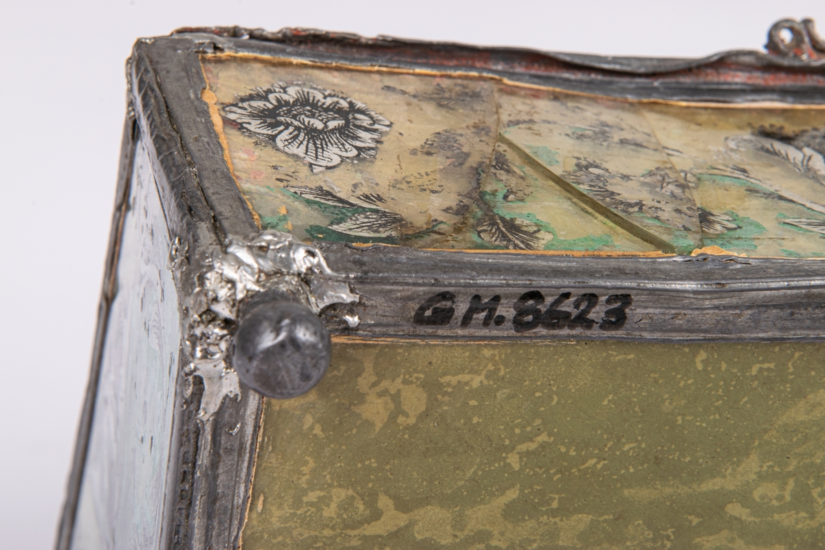 """Kat.kort: Syskrin. Överst grön nåldyna. Formen är pulpetartad, sidorna bestå av målade glasskivor med blylister emellan. Målningen är grön med blomornament i svart och silver. Gult papper under. Locket rör sig på två gångjärn och hålles innuti av en tunn kedja. I locket under nåldynan finnes en liten spegel med målning i grönt """"W.E.M. 1767"""", med kunglig krona över samt växtranka omkring nertill. Skrinet står på fyra små kulfötter av bly. På ena fältet av locket ser man glasmästareämbetets sigill. Gävle, Gästrikland."""
