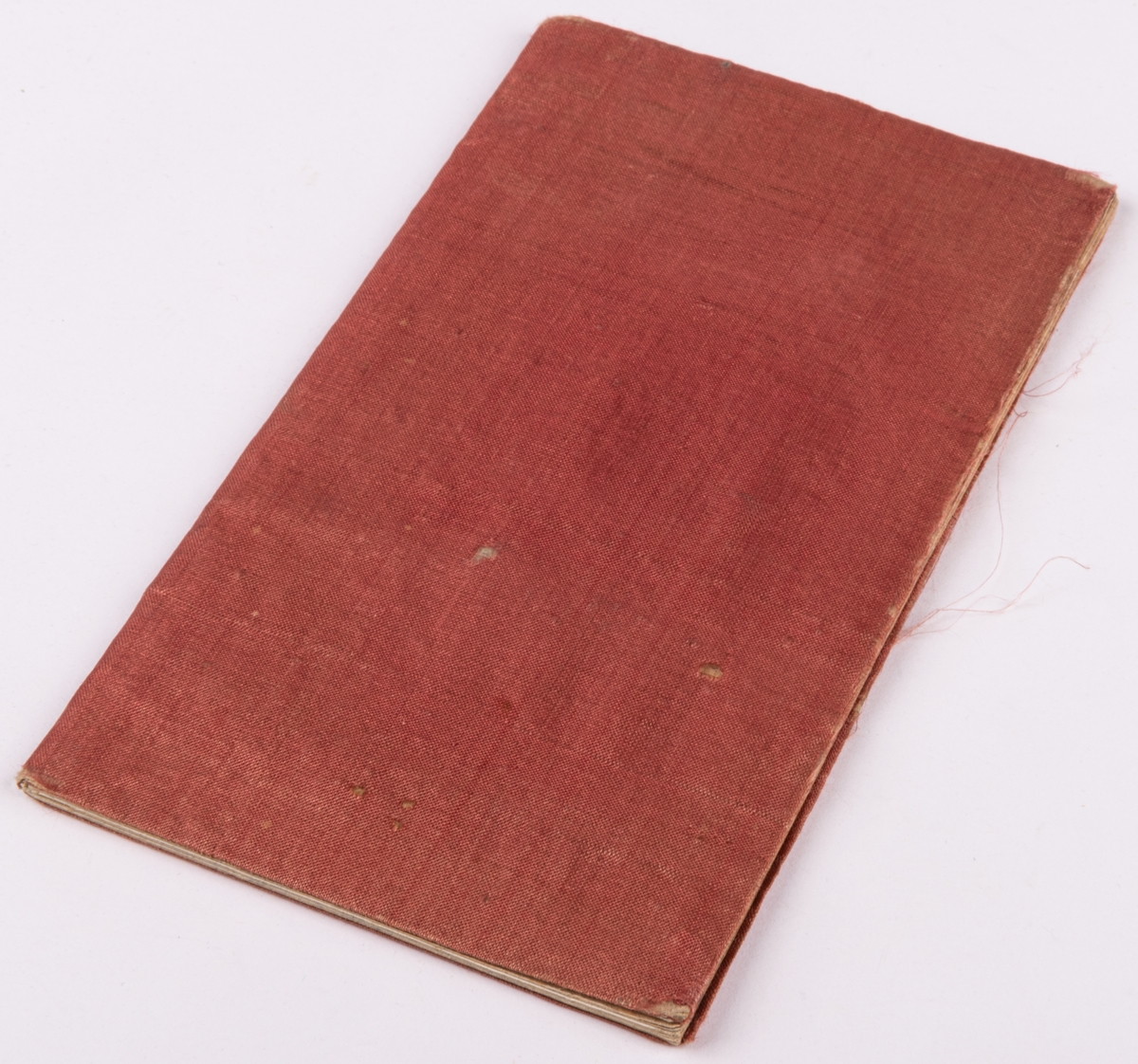 """Anteckningsbok klädd med rött siden. Inuti skrivet  """"Från Clara Nordblad julafton 1848""""."""