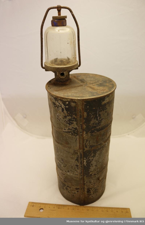 En lanterne med liten lampe og brenner og stor gassbeholder. Beholderen er i sylinderformet metall, og selve lampen er laget i glass. Beholderen har vært malt i svartmaling, men den har for det meste flasset av, og er nå preget av mye rust. På undersiden av gassbeholderen er det to hull i midten.