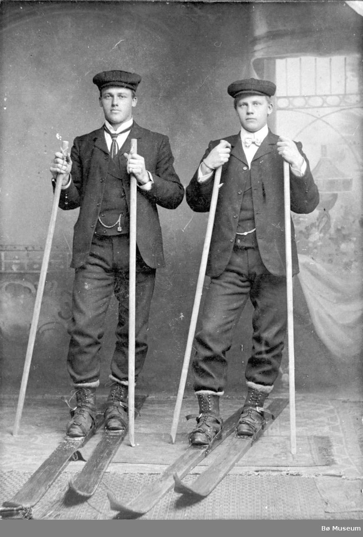 Helland Brothers, Knut G. Helland t.v. og Gunnar G. Helland t.h. på ski inne i eit fotoatelier.