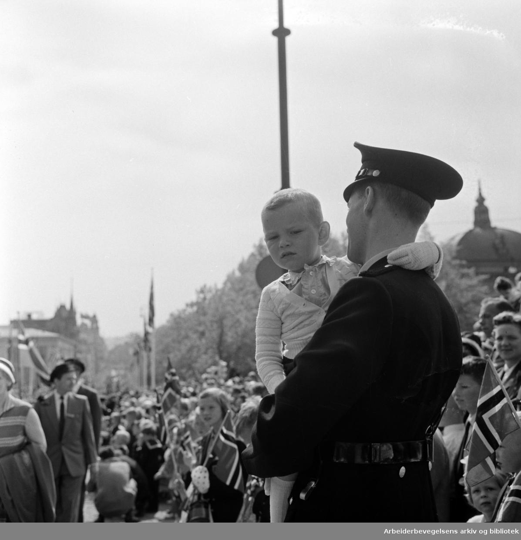"""""""En liten engelsk gjest kom bort i vrimmelen og ble tatt hånd om av en påpasselig konstabel"""". Barnetoget. 17. mai 1960"""