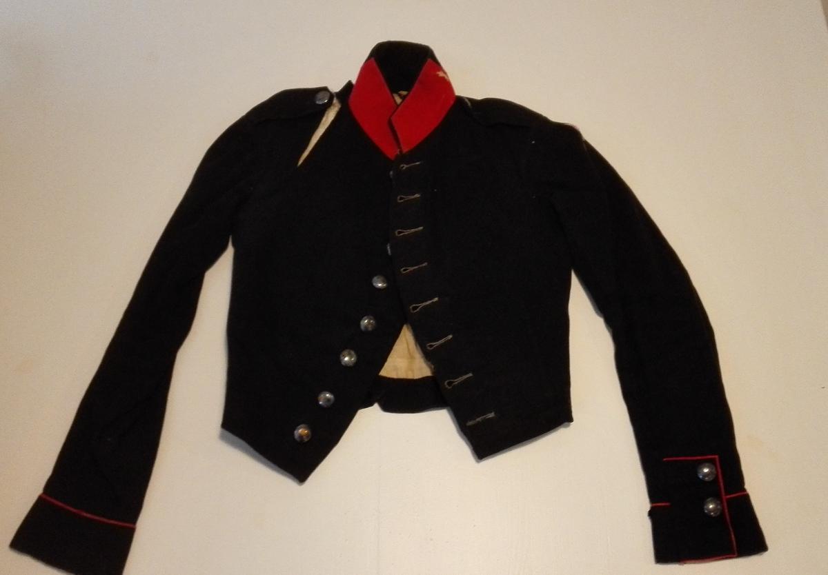 1 uniformslue og trøie.  Kadetlue og trøie benyttet av min avdøde far i 1848 som kadet. Baade trøien og luen har mærket 52. Gave fra G.F.Heiberg, Amble.  Sjå katalognr.7025