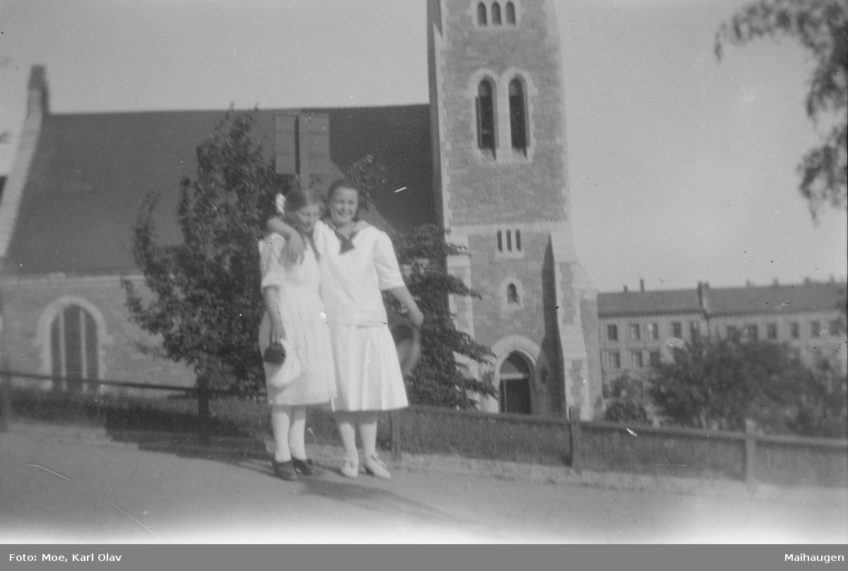 To unge damer fremfor en kirke i en by