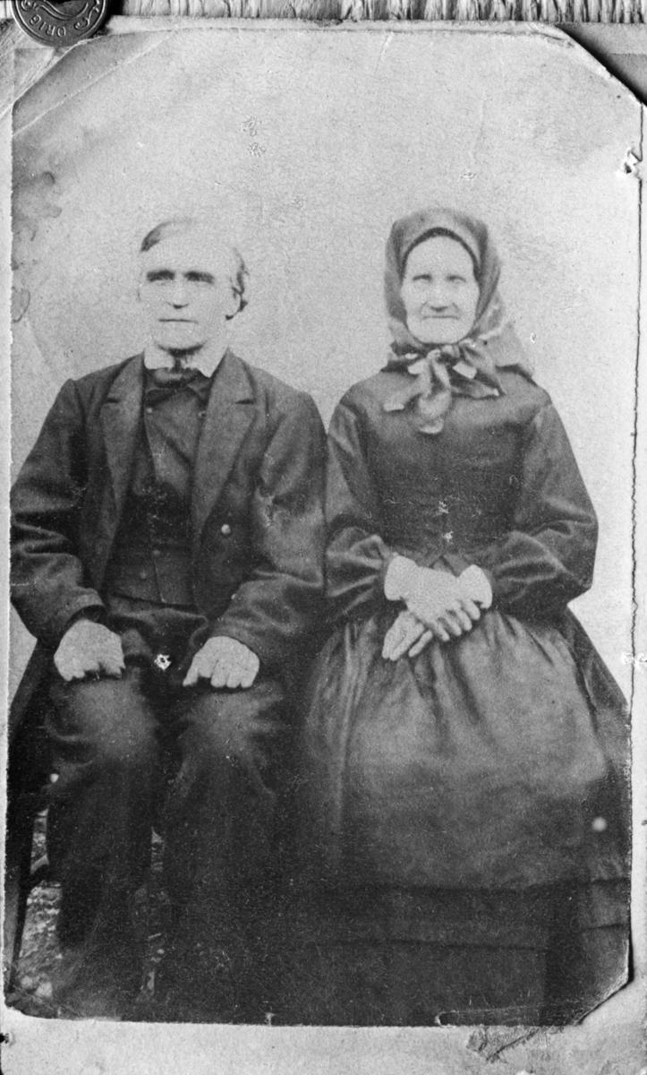 Eldre ektepar med kone i kjole og skaut og mann i mørk dress, repro
