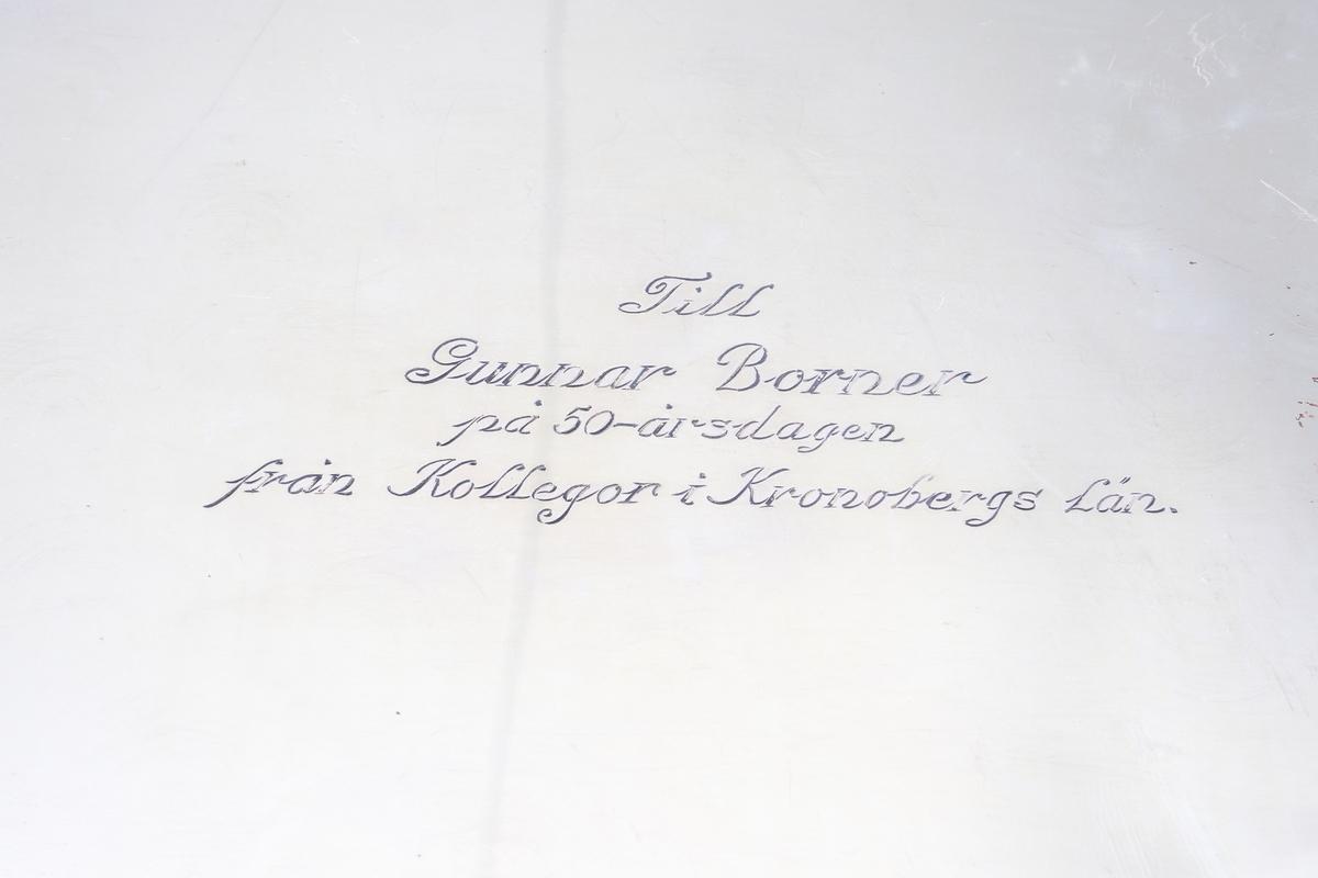 """Fat av silver. Ovalt prydnadsfat, med pressad dekor i hög relief på brättet, bestående av blommor och bladornament. Brättet är försett med två bekransade ramar, i den övre kanten är ett graverat monogram: """"G B"""". I den undre kanten står: """"19 22/12 35"""". På fatets baksida finns följande text: """"Till Gunnar Borner på 50-årsdagen från kollegor i Kronobergs län"""". Stämplar på brättets undersida."""