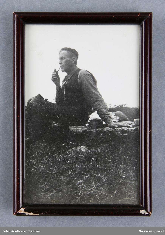 Man, sittande profil, i naturlandskap, rökande pipa.