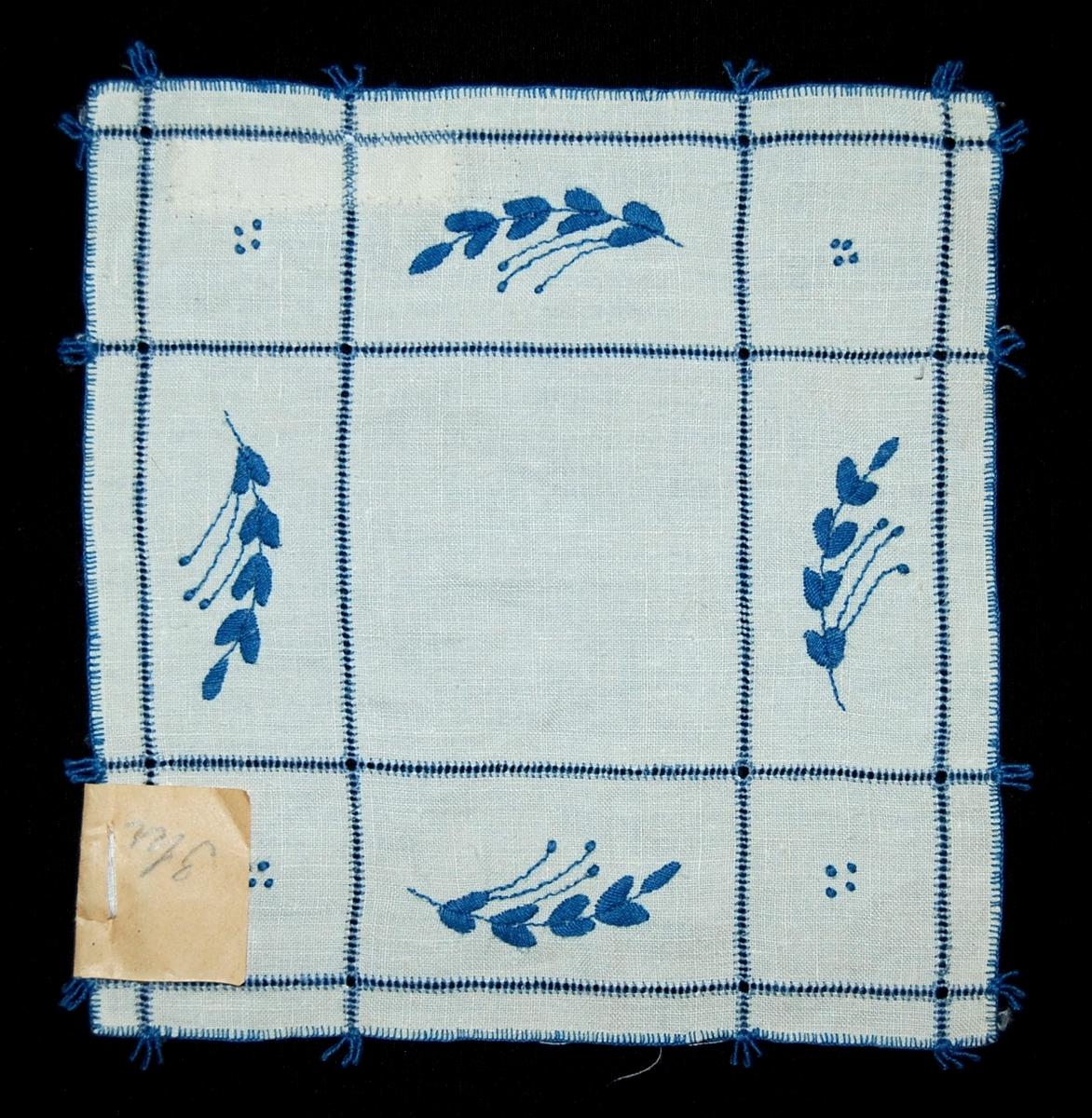 """Av vit linnelärft, rutindelning sydd i enkel utdragssöm med blått bomullsgarn, i rutorna bladkvistar resp. små prickar broderade i plattsöm och stjälksöm med blått garn, langettsöm runtom, små sydda """"tofsar"""" i kanten. Prislapp fastnålad: 3 kr, skrivet med blyerts."""