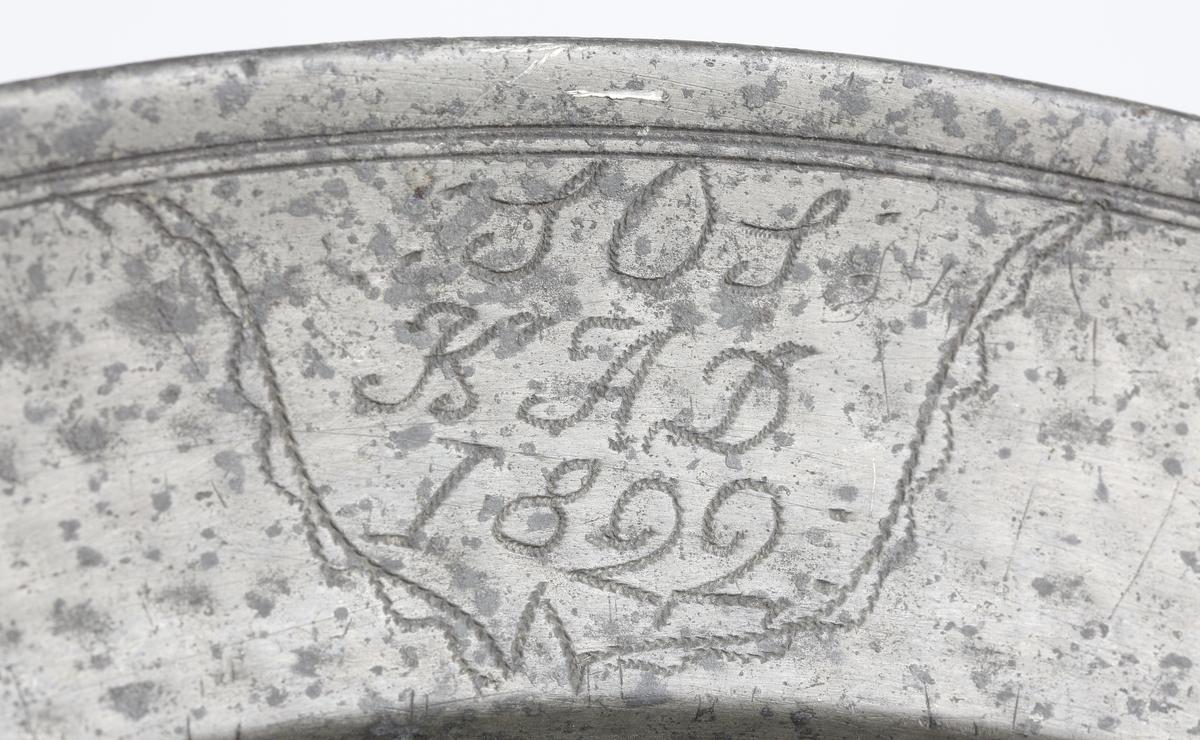 """Fat av tenn. Runt, hamrat stekfat. Brämen avslutas med rundstav. På brämens ytterkant finns två graverade monogram inom en bård: """"S.O.S., K.A.D., 1822"""". På brämens undersida finns graverat ägarinitialer: """"I.V.R."""". Stämplar på brämens översida."""
