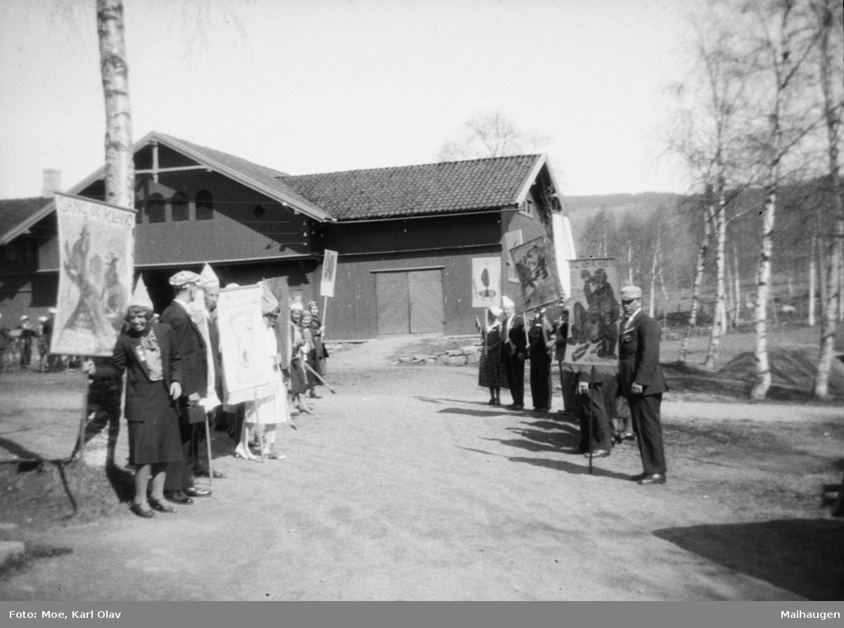 """Fra et musikkstevne på Kornhaug, Follebu. Faneborg, hvorav en har påskrevet """"Sang og Klang"""". Noen av personene med sangerluer og noen med spiss hatt."""