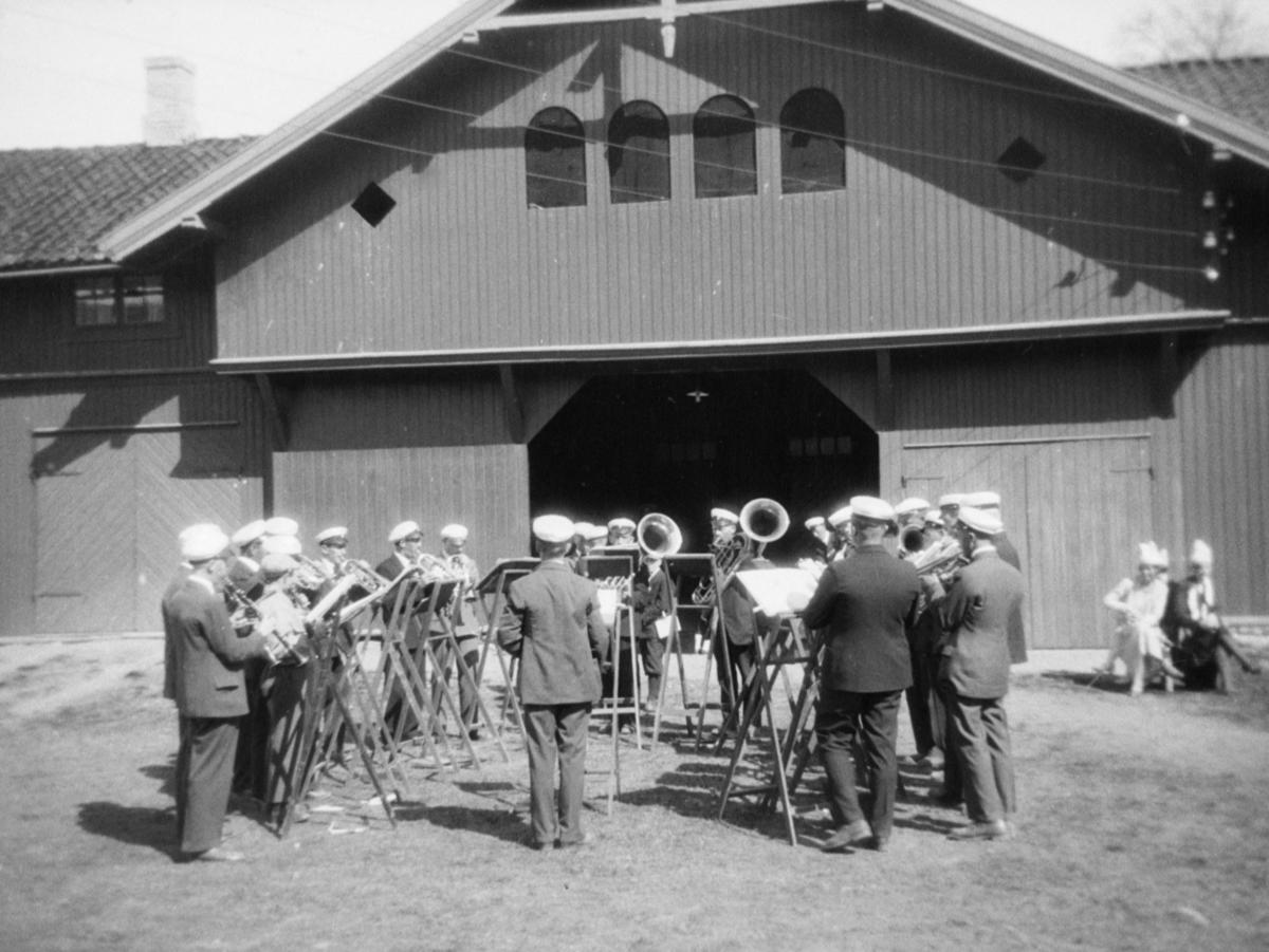 Musikkorps som spiller utenfor en stor bygning på Kornahug, Follebu.