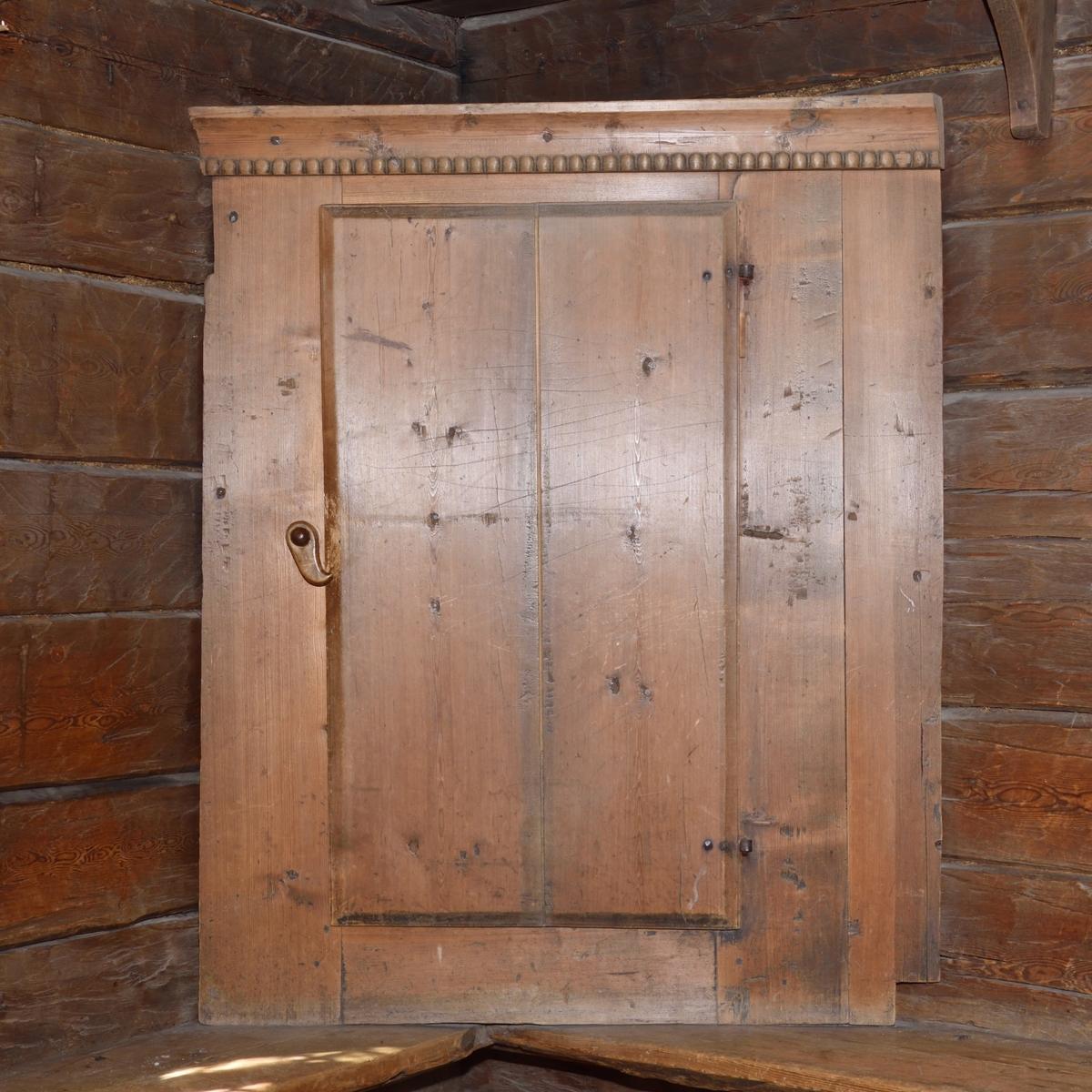 Hörnskåp av trä med bred dörr. Stänges med vridregel av trä. Gångjärn av metall. Avslutas upptill med skuren pärlstav. Invändigt ett hyllplan. Saknar bakstycken och botten, direkt monterad mot vägg.