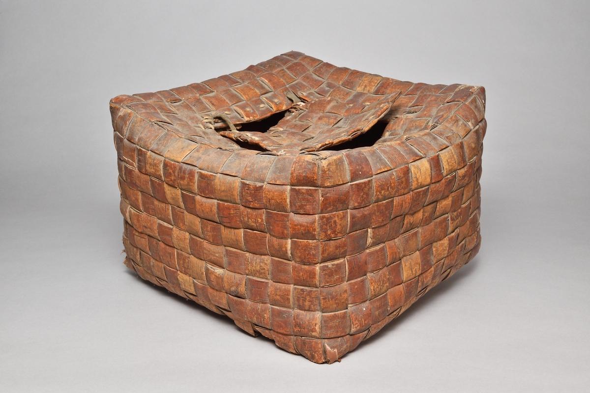 Mjölskäppa av flätad näver, kubisk med fyrkantigt hål på ovansidan med näverlock fäst med gångjärn av läder.