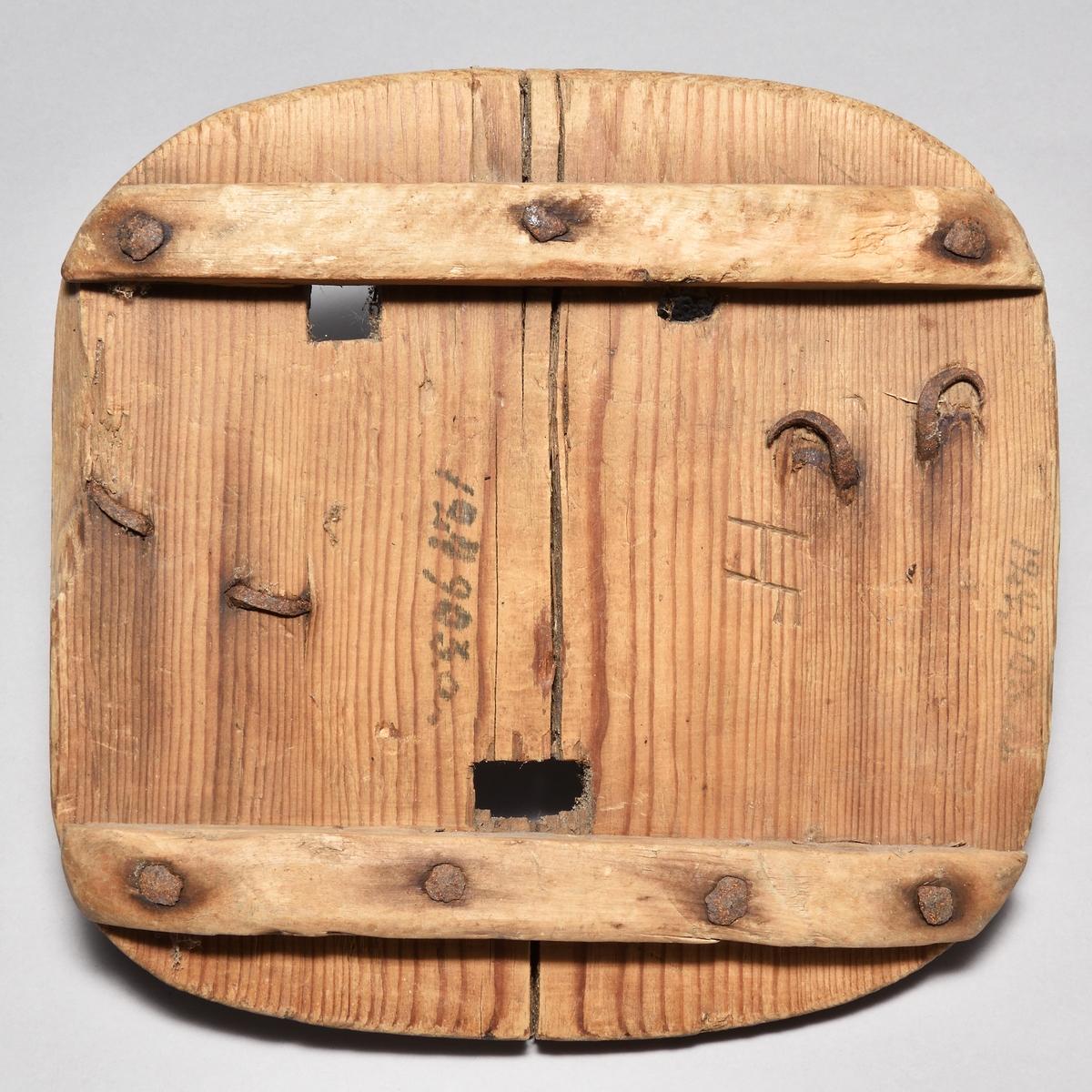 """Hästtrygor, 3 st, av furu, alla av samma form: fyrkantiga med rundade hörn. På undersidan två påspikade tvärslåar av björk. Tre hål för broddarna, bindslen i form av hasp av järn. Märken efter hästskon. A märkt med """"HF"""", B med """"HB"""" och C med """"WA""""."""
