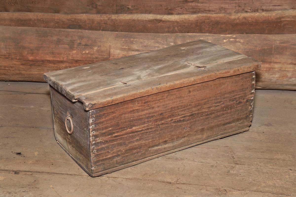 Kista av omålad furu, rektangulär med plant lock på gångjärn. Sidorna och botten fastsatta med träplugg. Locket urholkat, med fals som omsluter kistans sidor. Två ringformiga sidohandtag.