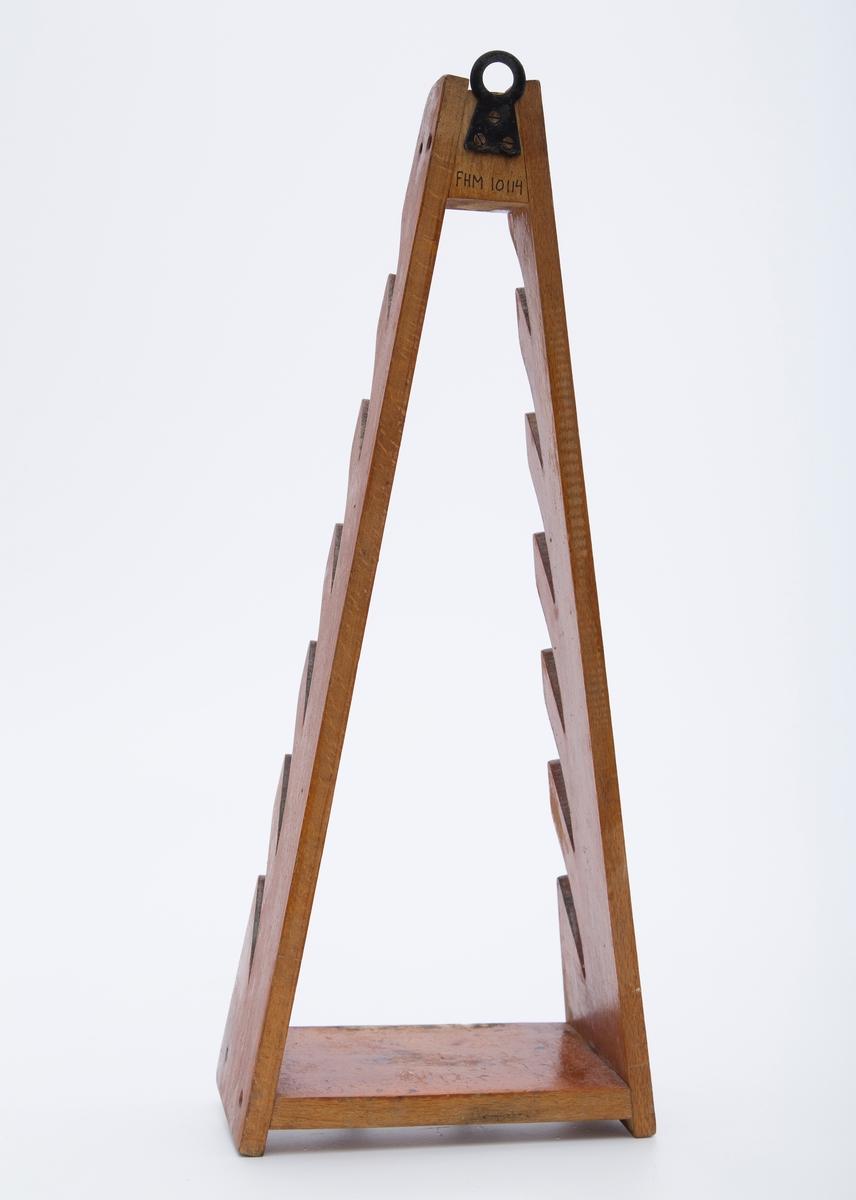 Stativ til grytelokk i lakkert tre og metall. Trekantform med håndtak i metall mederst på stativet.