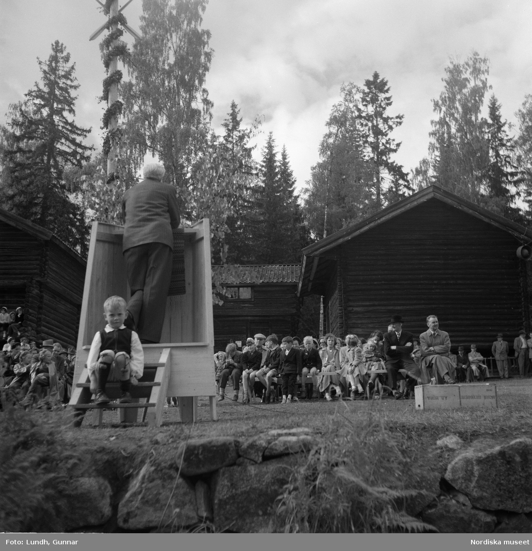 Motiv: (ingen anteckning) ; Två män i folkdräkt håller fioler, en man i en talarstol talar till en folksamling, ett barn sitter på trapan till en talarstol, en folksamling vid en midsommarstång, porträtt av två varav ett i folkdräkt, kvinnor och män i folkdräkt dansar vid en midsommarstång.