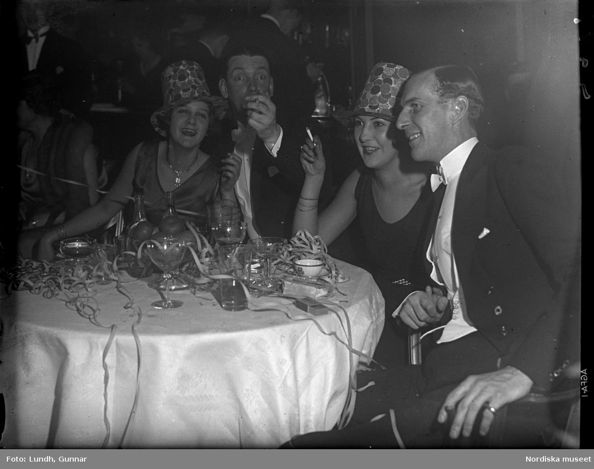 Motiv: (ingen anteckning) ; Interiör med en flicka som sitter vid en julgran och håller en docka, en katt sitter på en kudde vid en ljusstake, interiör troligen från Grands Vinterträdgård med festklädda människor som sitter vi bord och äter och en orkester som spelar - möjligen vid nyårsfirande.