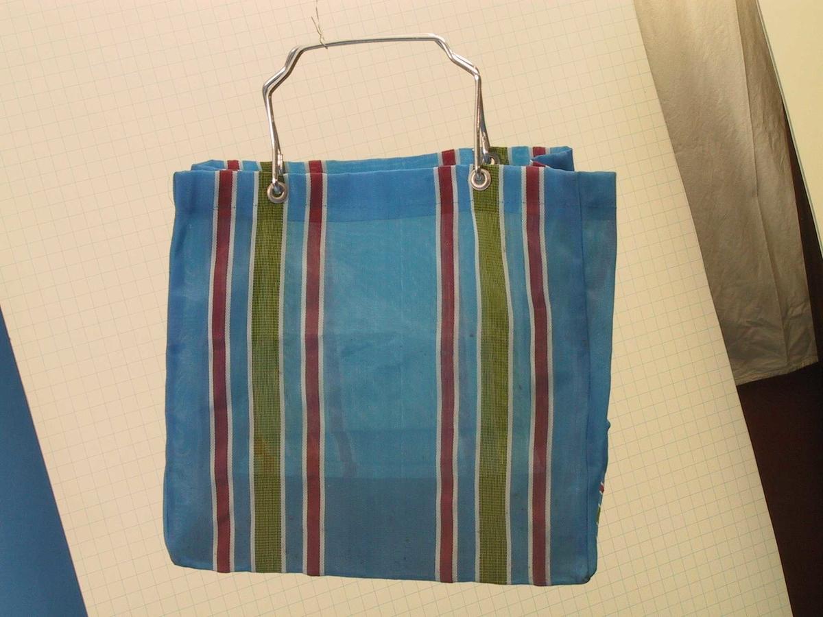 Bærenett av vevd plastduk med handtak av jern. Blått med striper i rødt, hvitt og gul.