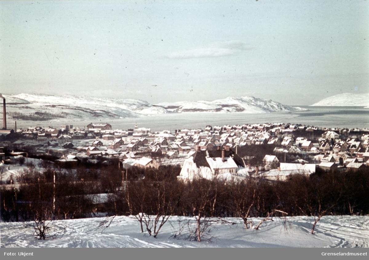 Kirkenes sett fra Prestefjellet. Fra venstre i bildet ser vi Dampsentralen, skolen og så kirken. Fjorden har et tynt islag.