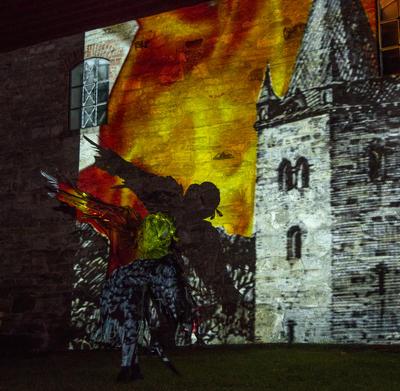En svart fugl flyr foran en videoprojeksjon av middelalderkatedralen som brenner.