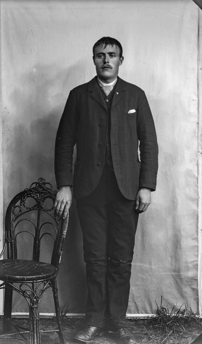 Mann som står ved siden av stol laget av rotting, kledd i kvit sjorte og mørk dress