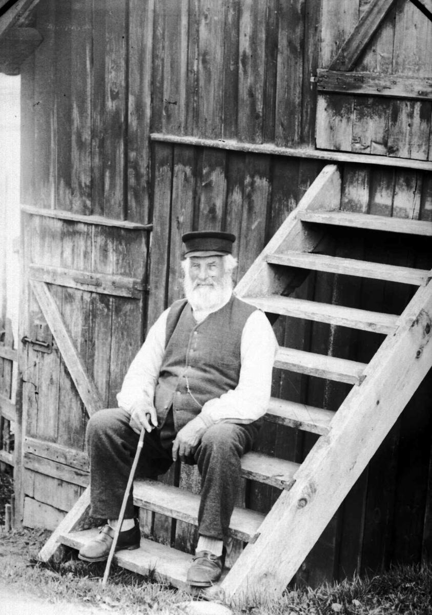 Eldre man sittende på trapp i bakgård.