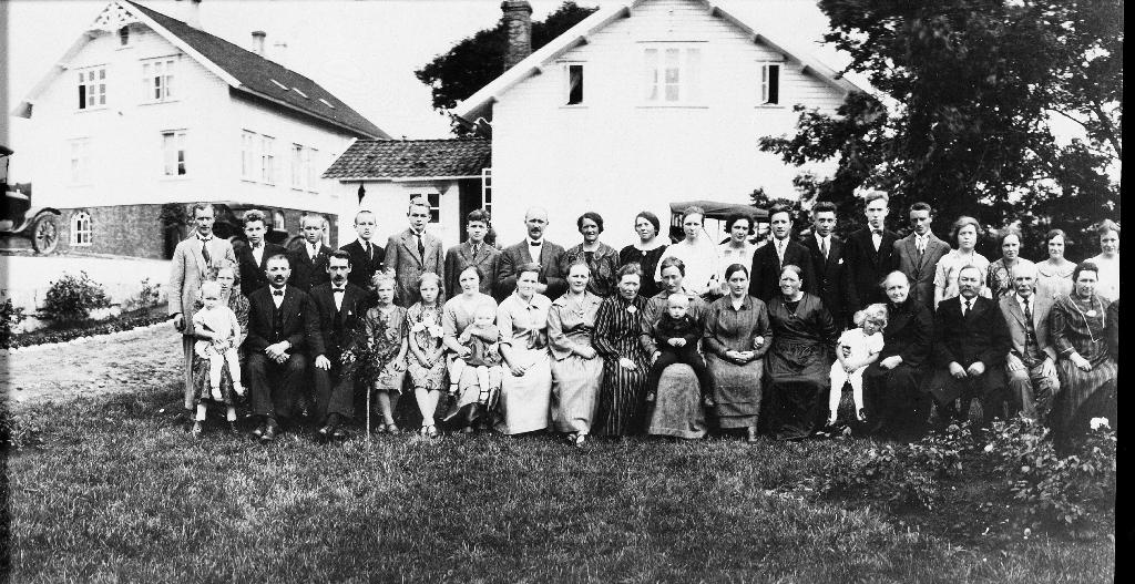 Familie på vitjing frå USA. O. G. Kverneland med kona Anna (f. Aasland) og 13 barn. Huset til venstre er Storhuset. Til høgre privatbustaden til O.G. Kverneland, Gubbahuset. Same bilete som 1988.5TIM.17.005 og 1988.5TIM.4.001a