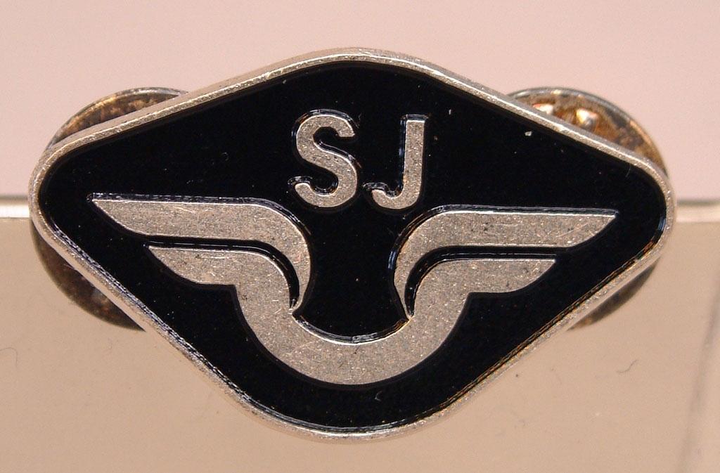 """Testuniform för tågmästare. Mörkblå herrkavaj, silverfärgade knappar med SJ-logga. Fickor med lock, tre små knappar på ärmen. På höger sida, rektangulär skylt med text """"Testuniform Tågmästare"""" Vänster sida SJ-logga med svart botten. Storlek 52."""