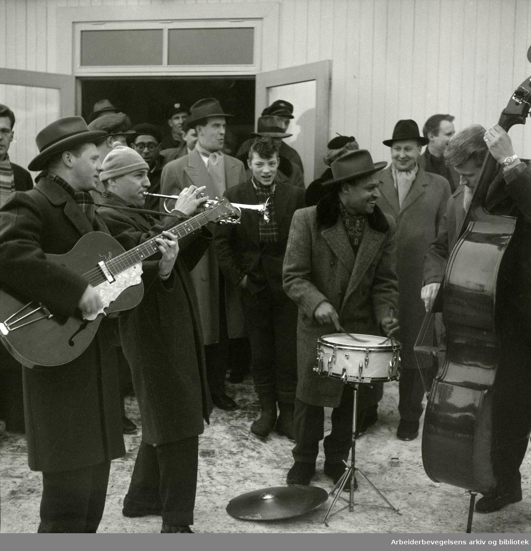 Jazz at the Philharmonic besøker Oslo februar 1956. Ankomst på Fornebu, hvor det ble gitt en velkomstkonsert. Fra venstre; Arne Bendiksen på gitar, Rowland Greenberg på trompet, Dizzy Gillespie (med briller), Jo Jones på trommer, Øystein Ringstad (med hatt) og Bjørn Pedersen på bass.
