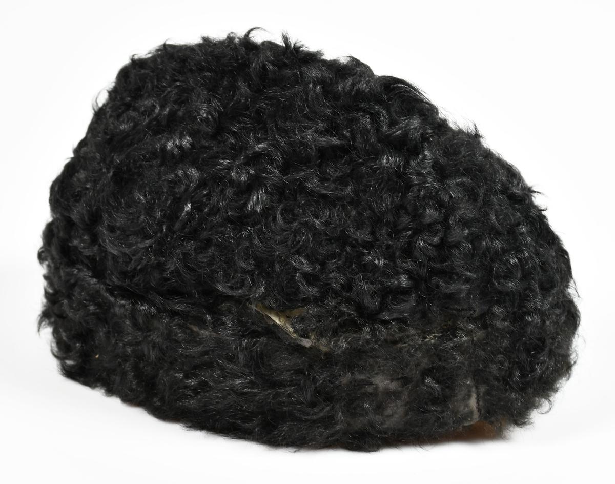 Anmärkningar: Svart persian, fodrad med svart siden. Gåva av Hakonbolaget V-ås.