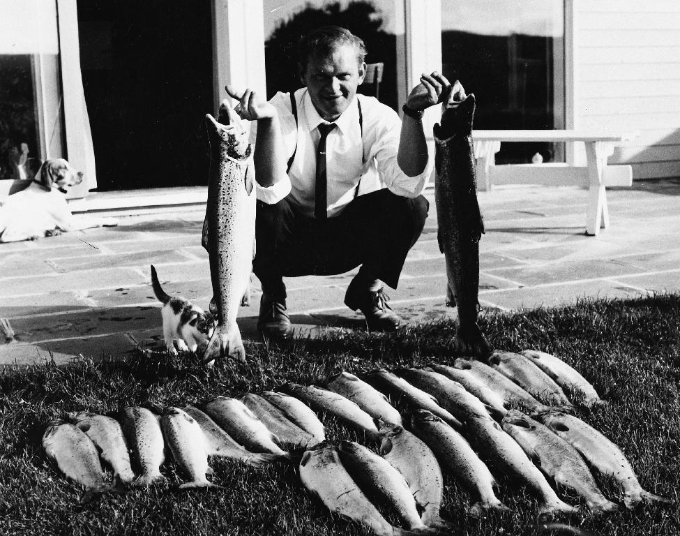 Ole Gabriel Kverneland (1927 - 1988) viser fram dagens fangst av svidde/laks fiska med flue.