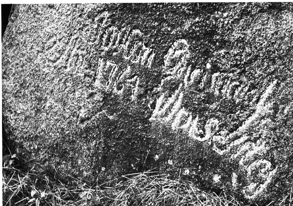 Stein med innhogd tekst. Årstalet 1764 er tydeleg - det andre er uråd å skjøna. Steinen ligg på garden til Sven T. Garborg i nærleiken av kopargruva.
