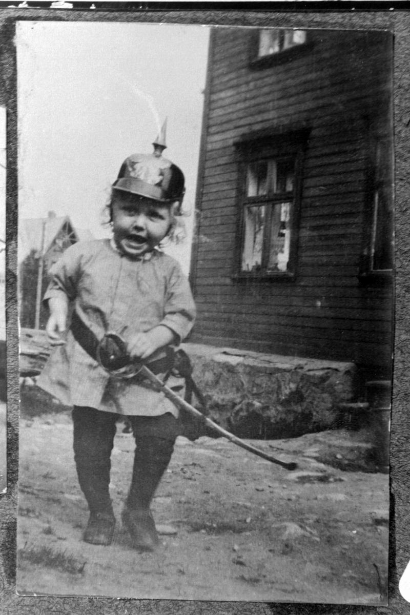Liten gutt med hjelm og sverd leker på en gårdsplass.