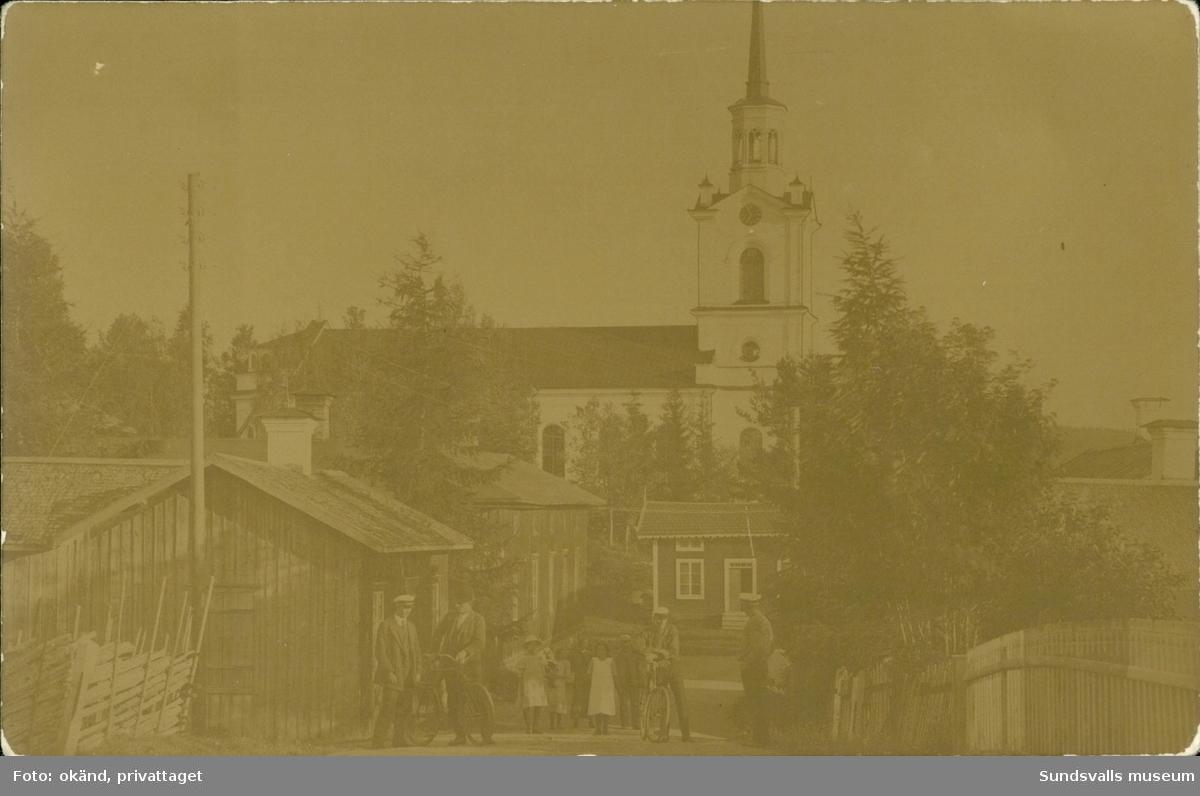 Vykort med motiv över parti av byn Liden med kyrkan i bakgrunden.
