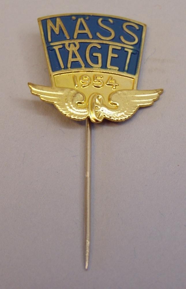 """Kavajnål: """"MÄSSTÅGET 1954"""" i guld mot blå botten, med Statens järnvägars emblem nedtill."""