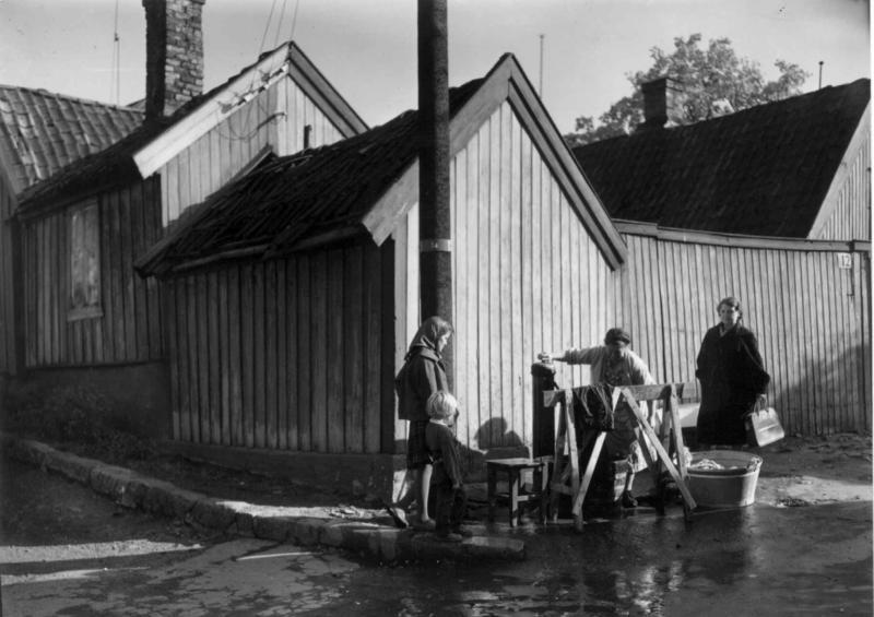 Klesvask ute ved vannposten foran Johannes gate 12/14 i 1959. (Foto/Photo)