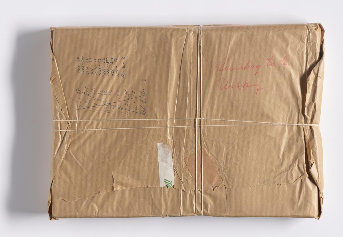 """Pakke med dokumenter innpakket i gråpapir. Rundt pakken er det knytt hyssing. Det er rester av tape med skrift foran og bak. På pakken er det skrevet i rød håndskrift: Aurskog (tre uleselige ord). Med blå penn er det skrevet """"1101 - 50, 1102 - 200, 1110 - 12, 1111 - 20, 1120 - 12, 1121 - 12, 1125 - 12, 1126 - 100, 1127 - 200, 1140 - 12, A. k. b. r. 2"""". Det er også skrevet en rekke tall som er krysset ut. Disse er: 1101 - 50, 1102 - 200, 1110 - 12, 1111 - 20, 1121 - 12, 1125 - 12, 1126 - 100, 1127 - 200, 1140 - 12, Arb. kr(?) bn(?) - 2.  NAV-samlingen er en gruppe av gjenstander som har vært anvendt på sosialkontoret (Aetat - NAV) i Skedsmo kommune."""