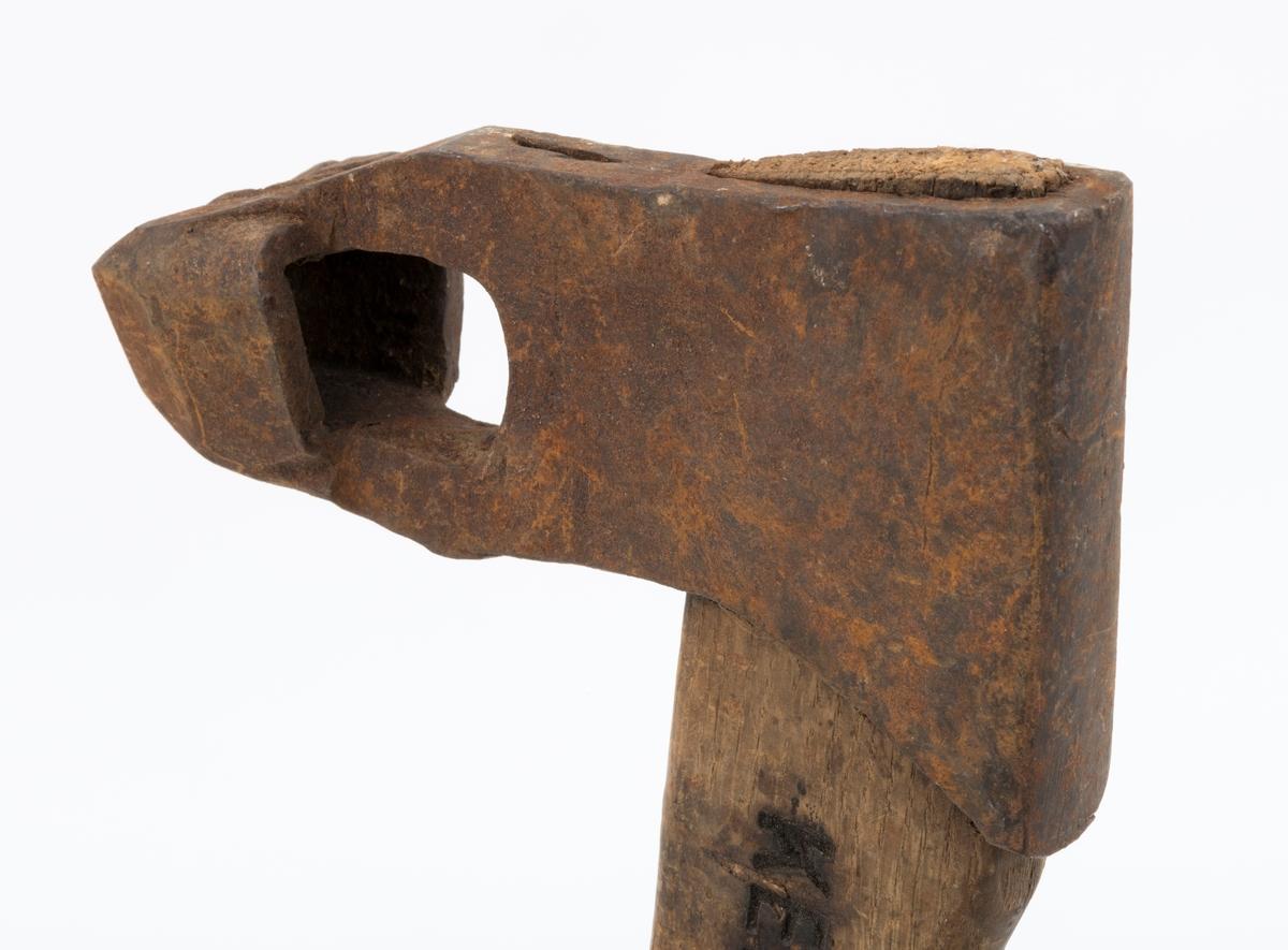 Øks - brukt til merking av fløtingstømmer i målings- og annammingsprosessen som foregikk langs vassdragene i overgangsfasen mellom vinter og vår, da tømmerstokkene etter måling formelt skiftet eier - fra skogeieren som hadde organisert hogst og framkjøring til sagbruk eller treforedlingsbedrift, som kjøpte tømmeret med sikte på videre bearbeiding til produkter som var salgbare på et større marked.   Øksehodet (den smidde delen) er 14,2 centimeter høyt fra eggpartiet til nakken. Nakkedelen er 7,9 centimeter lang, 2,5 centimeter bred bakerst og 2,3 centimeter bred foran. Øksenakken er noenlunde plan i lengderetningen. På venstre side av den nedre delen av øksehodet (bladet) er det utsmidd en 3,5 centimeter høy «sko» med profilert, fasslipt egg. Denne eggen ble slått inn i yteveden på fløtingsvirket, der den etterlot seg en profilert forsenkning, et symbol som tjente som sorteringsgrunnlag ved lenseanleggene i den nedre delen av vassdraget. På denne øksa minner eggprofilen om omrisset av ei krone. På høyre side av øksehodet finner vi smedstempelet «K. KNUDSEN  MJØNDALEN» samt avbildninger av medaljer denne produsenten hadde oppnådd på utstillinger. Øksehodet er rustent og stempelet er vanskelig lesbart.  Denne øksa har et cirka 60 centimeter langt, noenlunde rett treskaft. Som økseskaft flest er det bredest i høyderetningen og smalest i bredderetningen i den fremre enden, der den er skjeftet. Den bakre delen av skaftet er mer rundoval. Den fremre skaftenden er kilet med en trekile som skulle redusere faren for at øksa løsnet fra skaftet under merkingsarbeidet. Det forkortete firmanavnet «KELL-PARTINGTON» er påført den venstre sida av skaftet (sett i øksebrukerens perspektiv) ved hjelp av svijernstempel. Dette indikerer at øksa har vært brukt til å merke tømmer som ble innkjøpt på vegne av The Kellner Partington Paper Pulp Co. Lim., et engelsk selskap som fram til 1918 eide Borregaard-fabrikken i Sarpsborg. Navnet fortsatte å figurere på merkekartene også etter at Borre