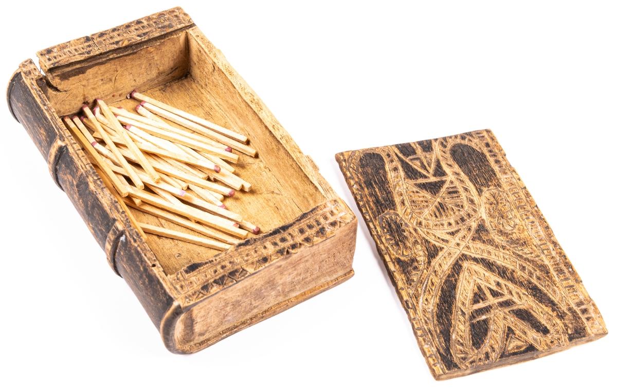 Kat.kort: Ask, av trä, i form av bok, med ena pärmen som skjutlock. Prydd med ristade ornament. Kan ha använts för tobak.