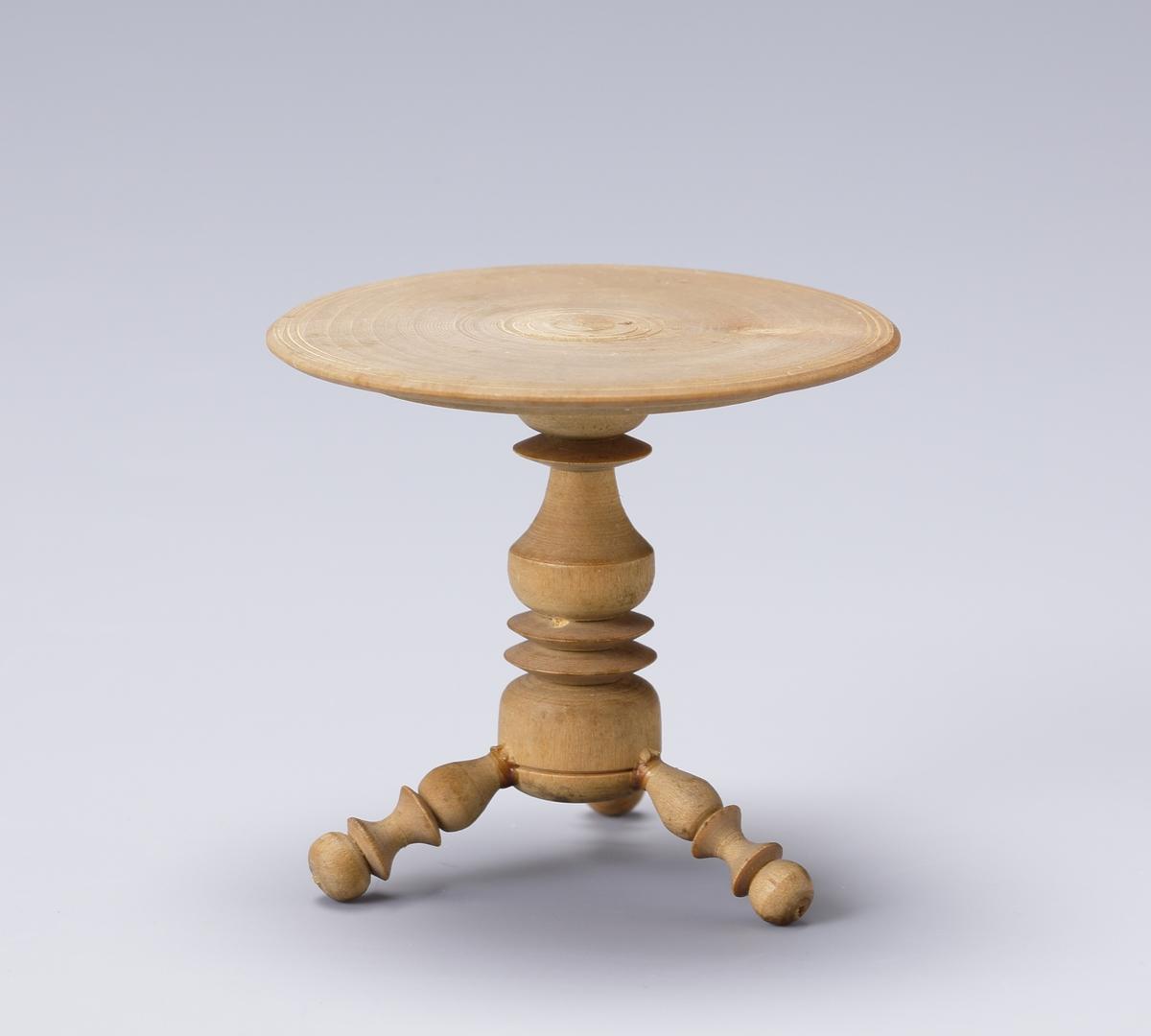 Dockskåpsmöblemang av furuträ: 5 stolar, 1 soffa och 1 bord, klädda med lila siden. Runt kanterna band och frans av blått bomullsgarn. Bordet svarvat.