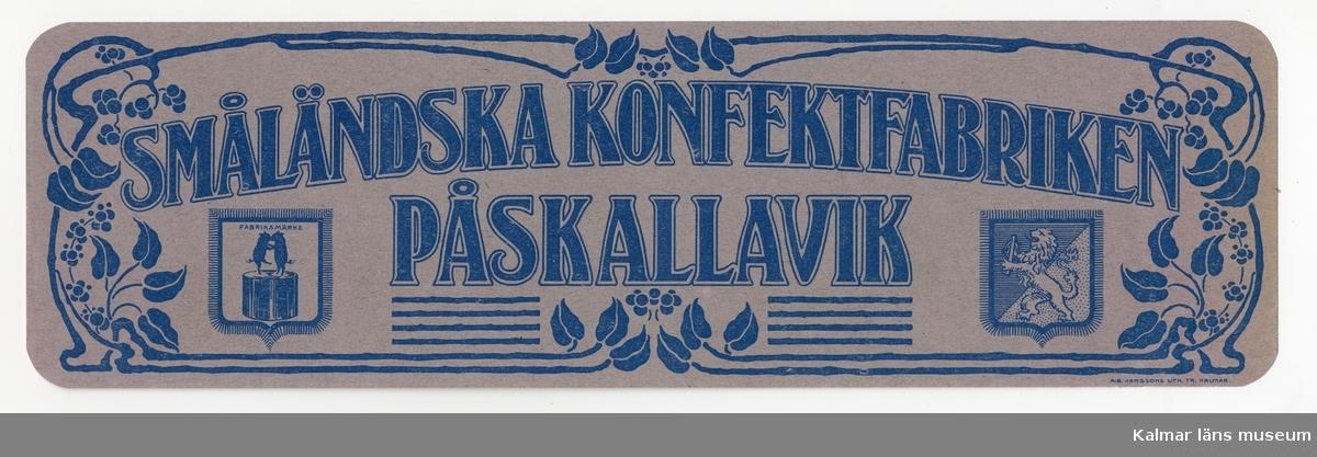 KLM 21360:3:6 Etikett, av papper, tryck av litografisk etikett. På etiketten text, Småländska konfektfabriken Påskallavik, samt fabriksmärke och landskapsvapnet för Småland. I färgen blått på grå bakgrund. Etikett till konfektförpackning. Beställare, Småländska Konfektfabriken, Påskallavik. Tryckt på Janssons Litografisk tryckeri i Kalmar. Trycket låg löst i provbok med varuetiketter mm, KLM 21360:1.