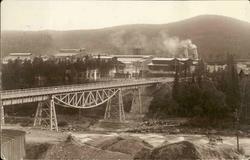 Vykort med motiv över fabriksområdet och gamla järnvägsbron