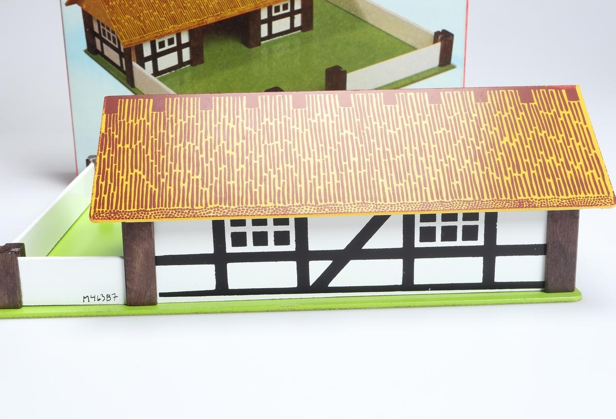"""Micki Lantgård, bestående av en grönlackerad masonitskiva, som har ett vitt stängsel med bruna hörnstolpar och en öppning framåt. På skivan står en ladugård, påminnande om korsvirkesstil, med halmtak. Ladugården är vit med bruna stolpar. Taket gult med brun """"halmimitering"""". Det går att lyfta av, med gavelspetsarna som är fastlimmade """"båspallar"""". Lantgården är förpackad i en vit och röd pappkartong med bild på, samt text på svenska, tyska, engelska och franska."""