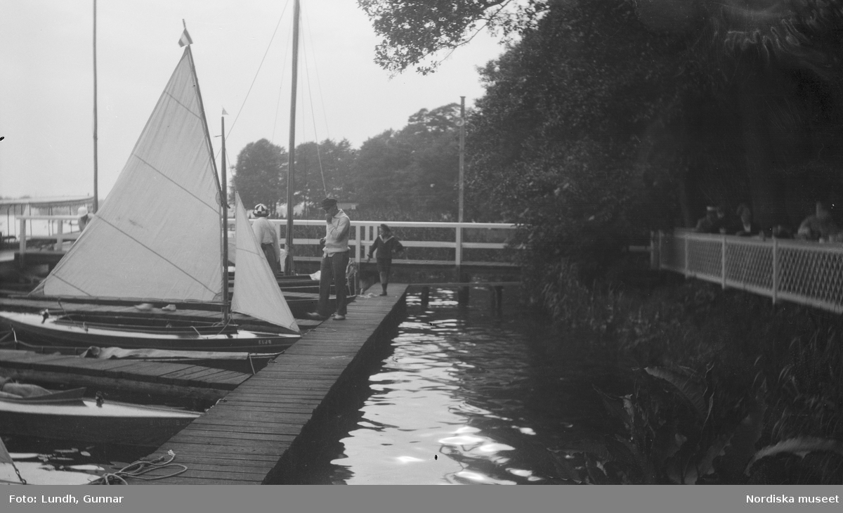 """Motiv: Utlandet, Berlins Omgivningar 157 - 177 ; En kvinna - en man och ett barn på en brygga i en hamn med båtar, anteckningar på kontaktkarta 175 """"Tiergarten detalj"""" 176 """"Fotograf i Grünewald""""."""
