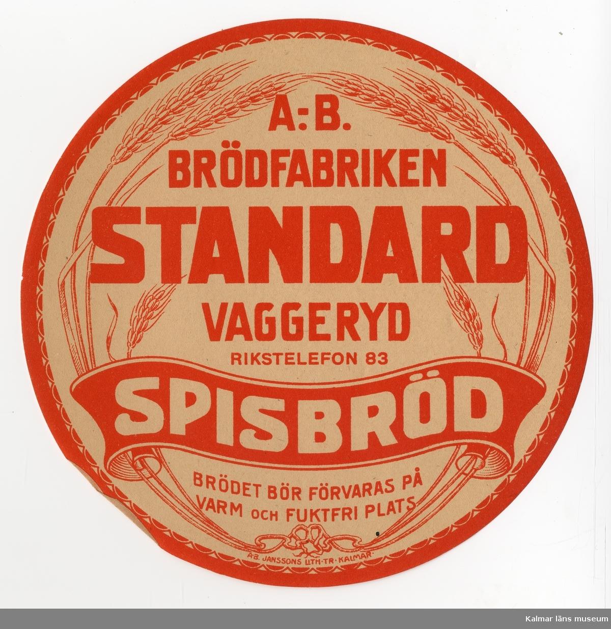KLM 21360:3:29 Etikett, av papper, tryck av litografisk etikett. På etiketten text: Standard Spisbröd. I färgen röd text på beige bakgrund. Etikett till knäckebrödsförpackning. Beställare: A.-B. Brödfabriken, Vaggeryd. Tryckt på Janssons Litografisk tryckeri i Kalmar. Trycket låg löst i provbok med varuetiketter mm, KLM 21360:1.