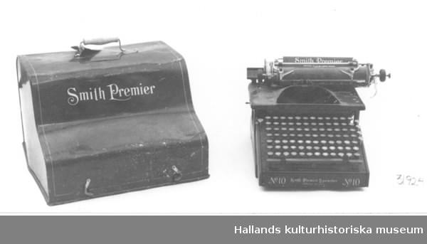 """a) Skrivmaskin. Längd: 26, 6 cm, bredd: 38 cm, höjd: 25 cm. Märke: """"No 10 Smith Premier Typewriter Syracruse, N. Y. U. S. A."""" Tangenter både för stora och små bokstäver samt för siffror och andra tecken. Svartmålad med guldskrift. b) Fodral. Längd: 40,5 cm, bredd: 40 cm, höjd: 30 cm. Plåt. Svartmålat. Text i guld: """"Smith Premier"""" Bärhandtag."""