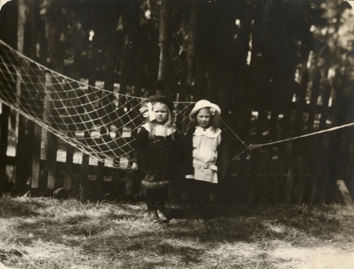 Porträtt av två flickor vid hängmatta.
