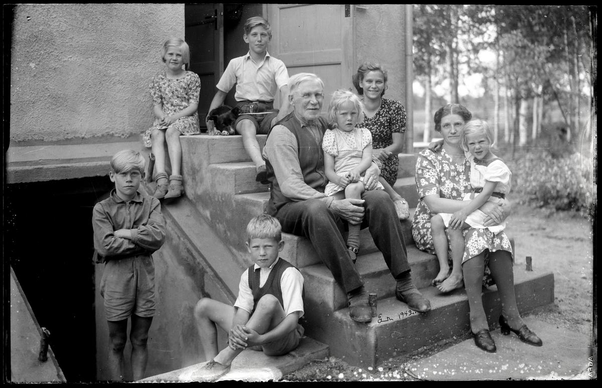 Stor familj framför hus