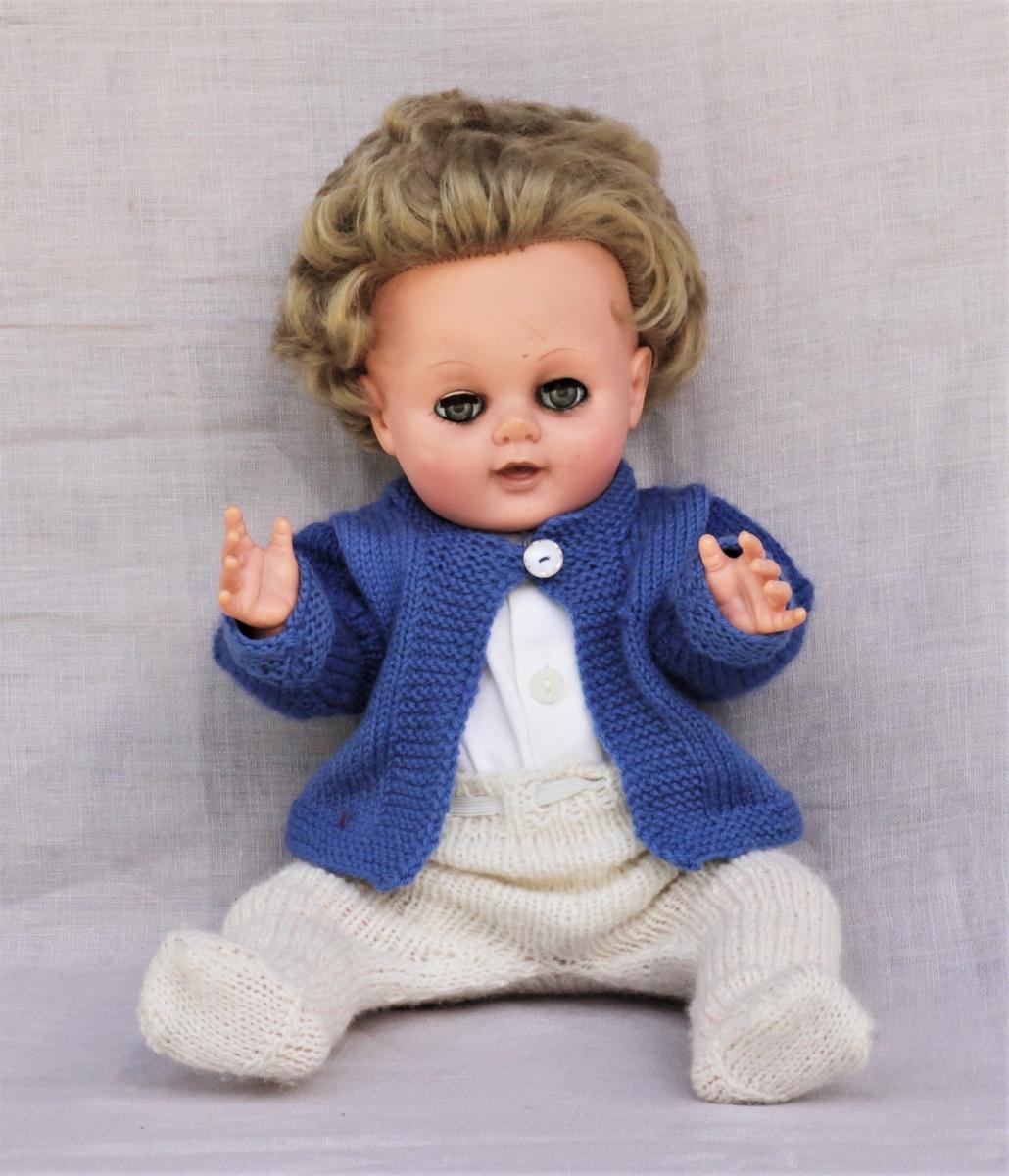 Dukke (a) med hvit, strikket ullbukse (b), hvit undertrøye (c) og blå, strikket ulljakke (d).
