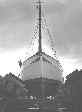 """Timmerman Sven """"Lille-Sven"""" i arbete vid slipen (fiskebåtsslipen). Fiskebåten är FG 8."""